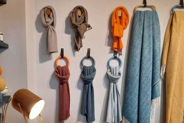 Modern wall hooks, hanging a display of scarves and blankets